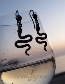 Minoan Silver Snake Earrings against beach sunset