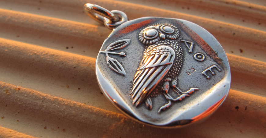 Wise owl coin pendant photographed outdoors